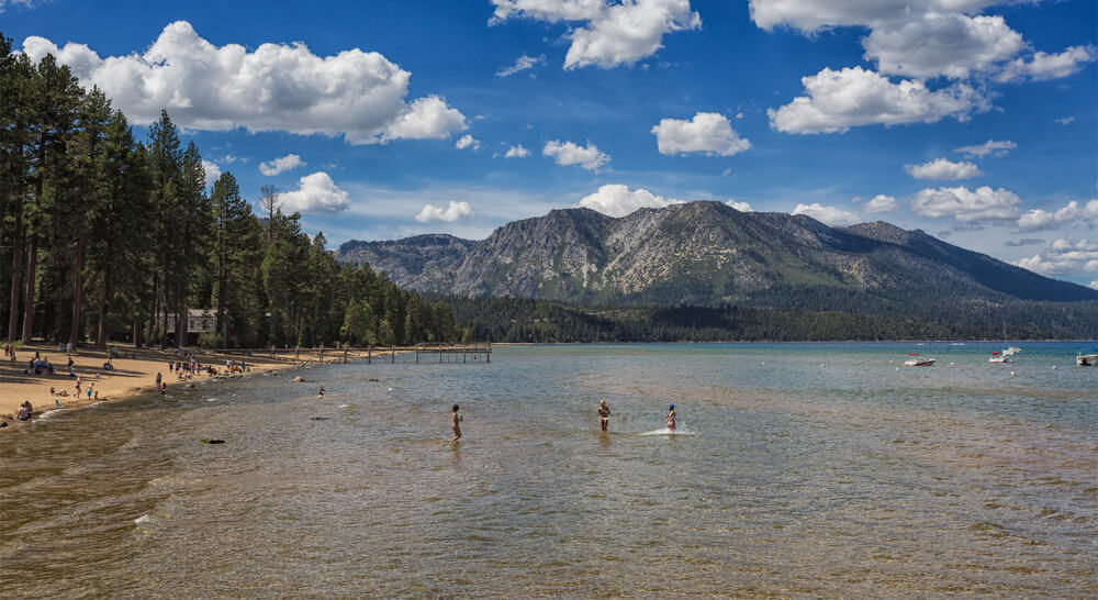 People playing in the shallow waters of Lake Tahoe in summer, other people sitting on the sandy shore of the lake, mountains and a partly cloudy sky in the background.
