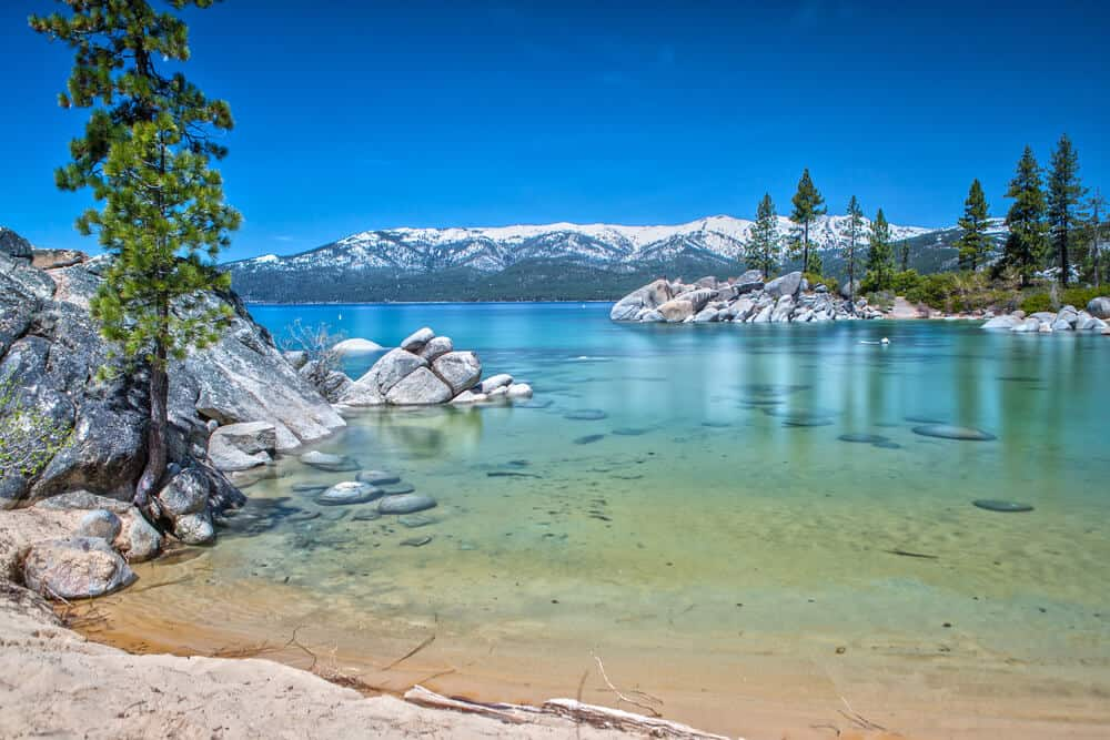 Extremely clear water ranging from light teal to deep turquoise on the shores of Lake Tahoe, surrounded by rocks and trees, with snow-covered mountains in the distance.
