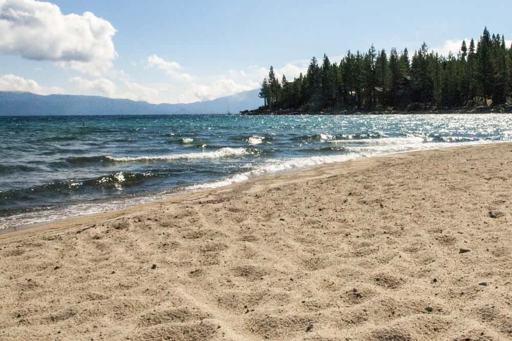 The fine sand at Meeks Bay Beach, water from the lake, and trees and mountains in the distance.
