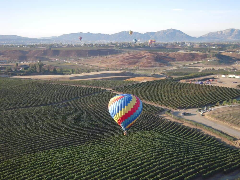A rainbow colored hot air balloon rising over the vineyards of Temecula, a popular Southern California road trip destination, with other hot air balloons way off in the distance.