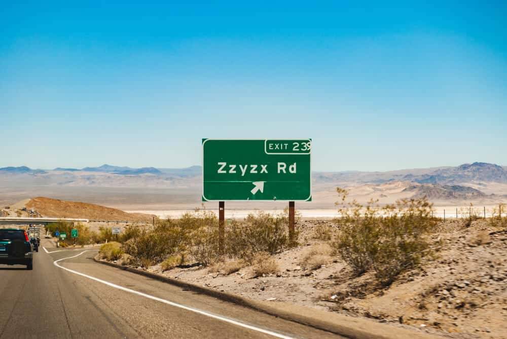"""A green street sign with white letters which reads """"Exit 23 Zxyxx Road"""" with some other cars on the highway out in the desert."""