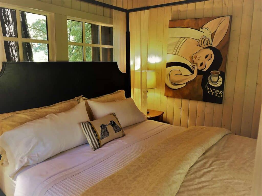 Cozy black bed with white sheets with detail of pillows and blankets on tp, white walls with a painting on it and trees outside the window