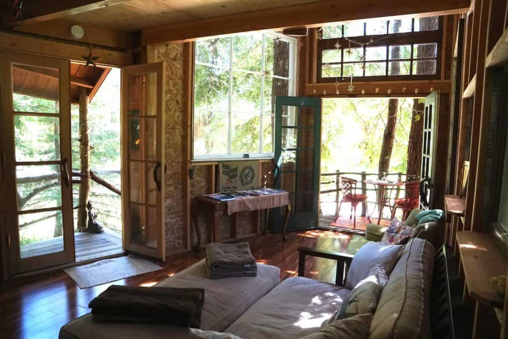 The living room of a South Bay Area California treehouse rental, with wooden details and comfortable, unpretentious furniture.