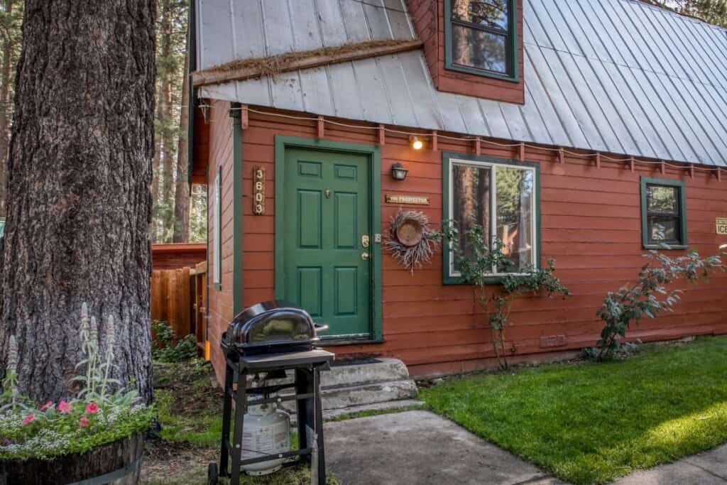 A charming pet friendly cabin in Tahoe with wood detailing, a green door, a BBQ grill in front and a small grassy area.