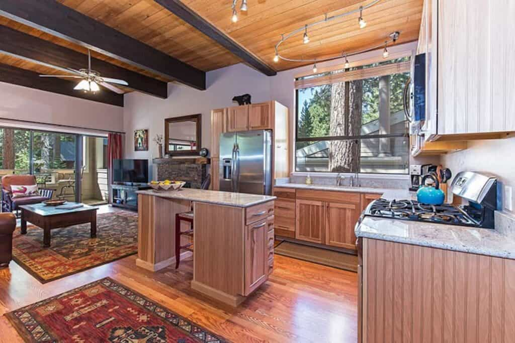 A modern condo in Tahoe with a gas range stove, kitchen island, living room with flatscreen TV and open floor plan.