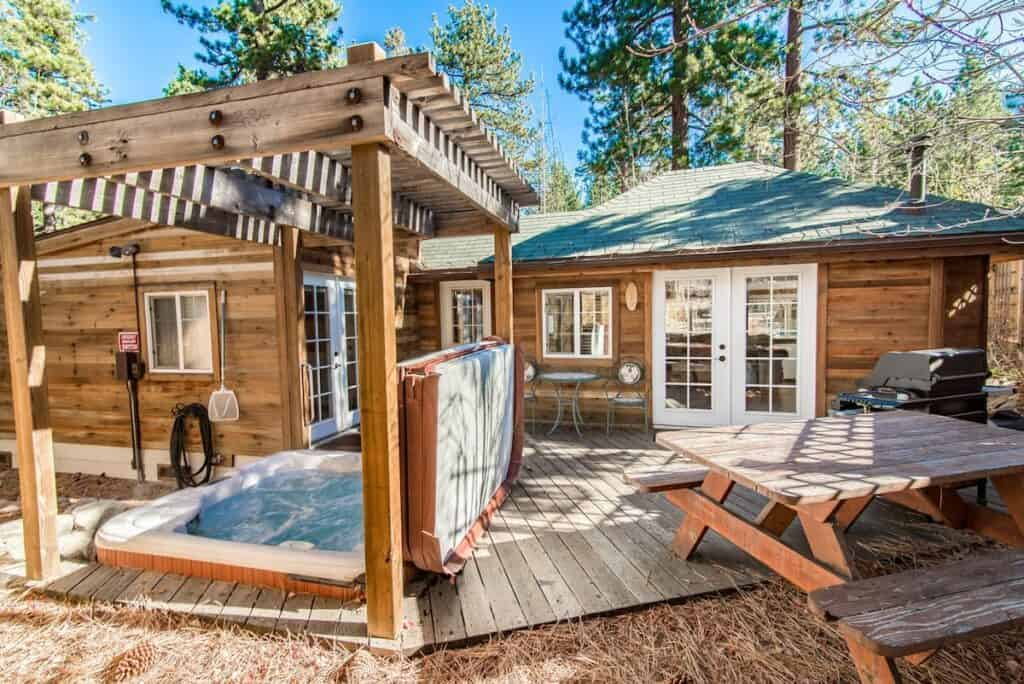 A wooden Tahoe Airbnb with a picnic table, grill, and hot tub available for use in the backyard.