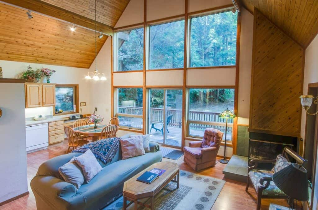 A cabin in Mendocino on Airbnb with floor to ceiling walls and wooden detailing with comfortable vintage furniture.