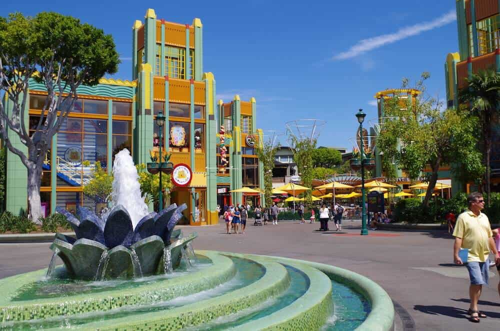People walking around Downtown Disney with a water fountain and buildings in the daytime.