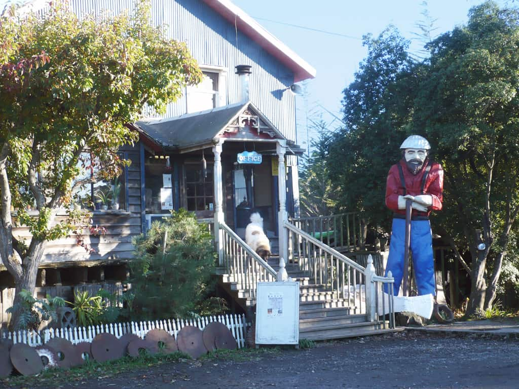 Statue of a man with a big ax wearing a red shirt and blue jeans and suspenders in front of the Blue Ox Millworks Museum. Dog on the staircase of the entrance.