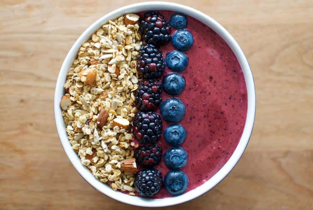 Purplish acai berry smoothie bowl with granola on one side and two stripes of berries: blackberries and blueberries