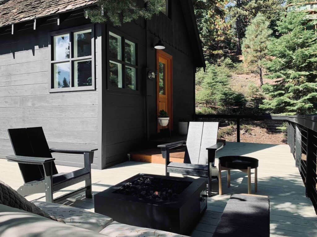 A small black cabin with an outdoor firepit and black seats outside on the deck, a popular Airbnb in Tahoe for couples and small groups.