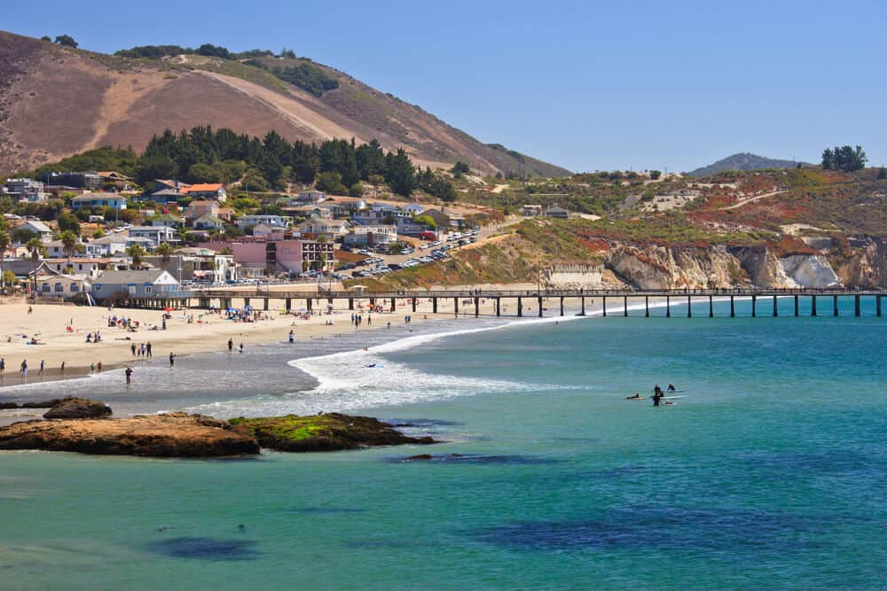 The beautiful waters of Avila Beach near San Luis obispo: caribbean blue waters with people on the beach and in the water, a pier stretching out into the ocean, and hills in the background.