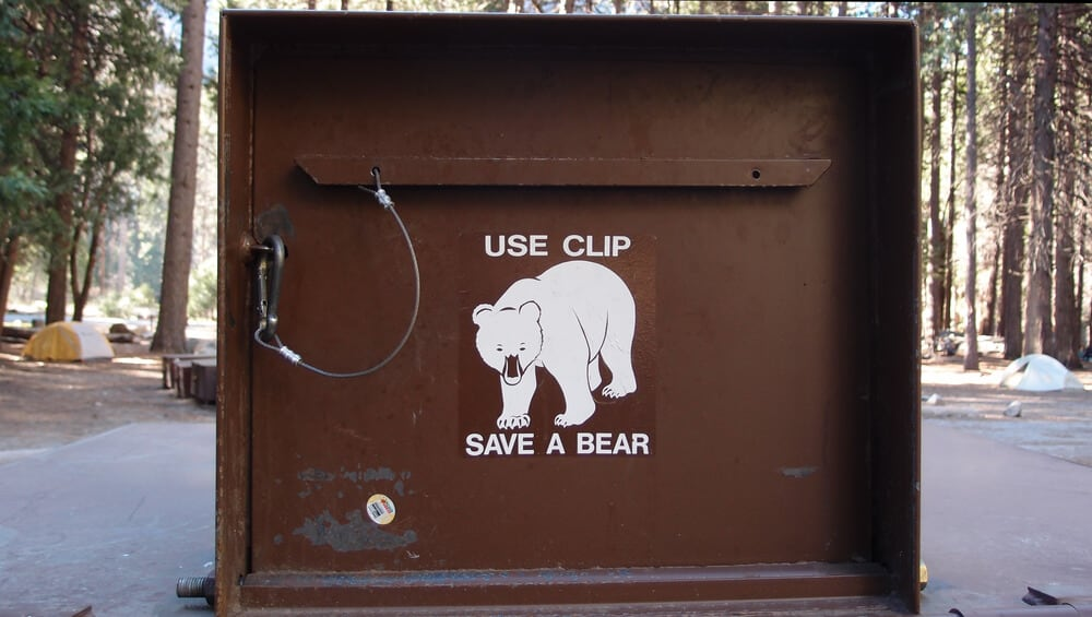 """Brown bear proof dumpster that says """"use clip, save a bear"""""""