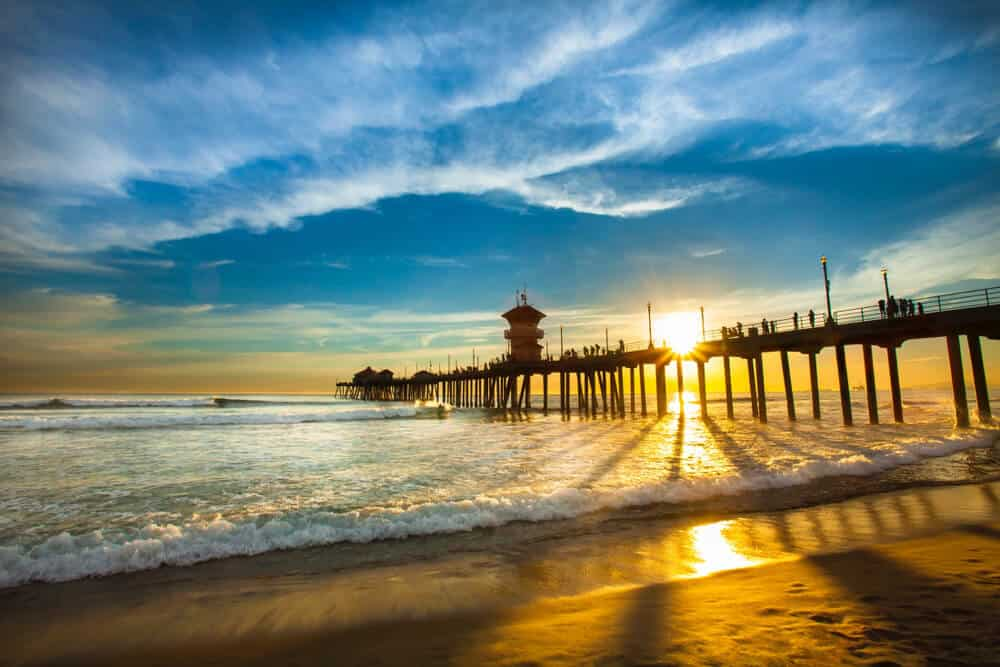 The famous Huntington beach pier at sunset with the sun sinking below the pier with a cloudy sky.