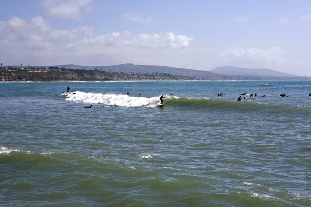 Surfers catching a small wave in Doheny State Beach, a famous beach in Dana Point made famous by a Beach Boys song. Surfing is another popular thing to do in Dana Point.