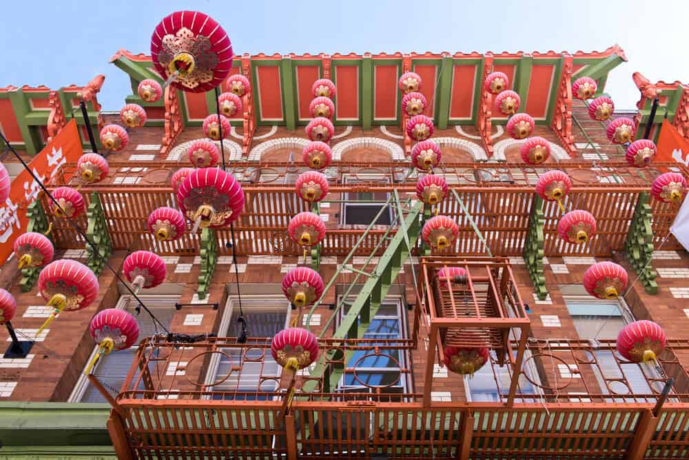 Red building with Chinese style lanterns dangling in front of it in a typical Chinatown builing