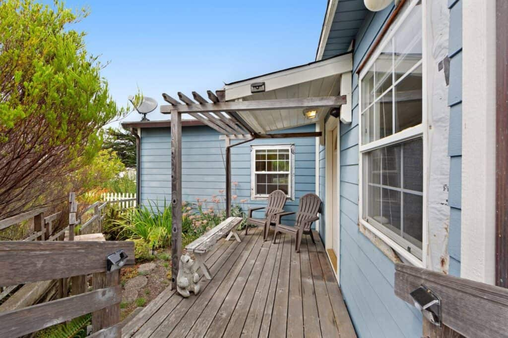 The exterior of a baby blue Mendocino airbnb cottage with a wooden porch with two chairs surrounded by plant life.