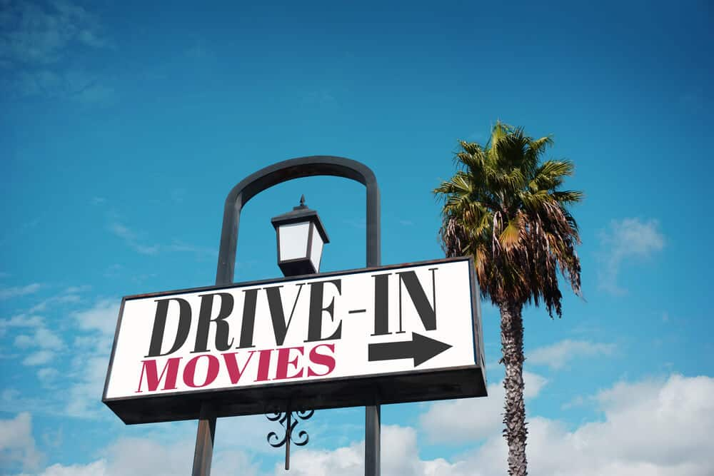 sign for drive in movies with palm trees in background