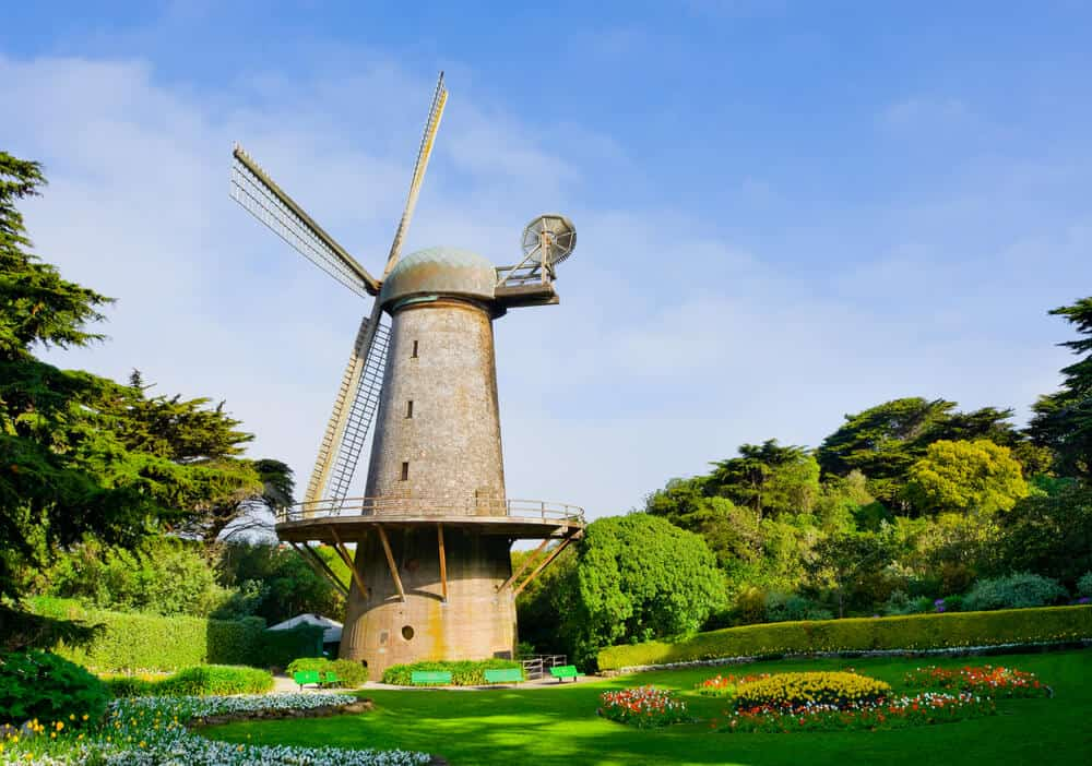 A stone dutch windmill in the middle of a San Francisco park surrounded by greenery and flowers.
