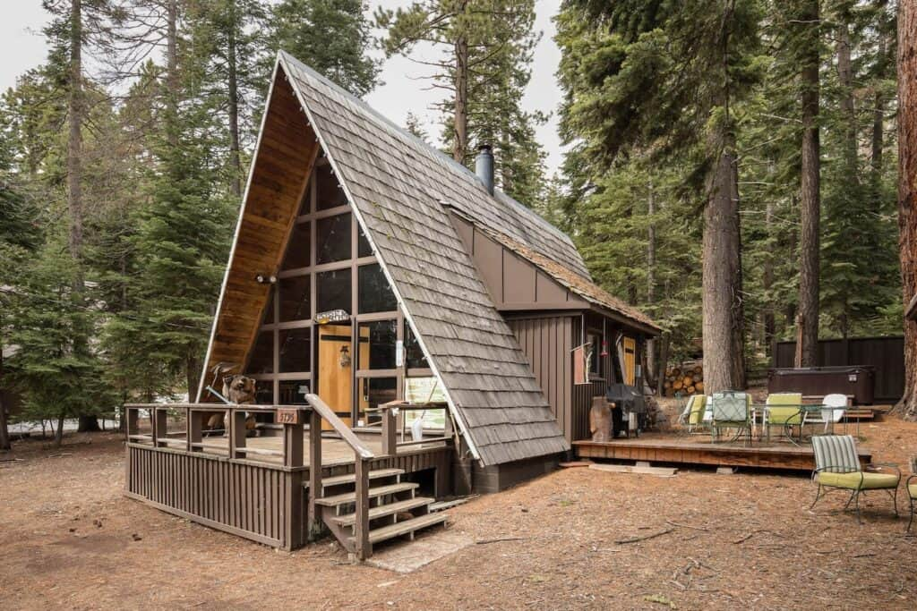 An A-Frame wooden cabin in Tahoe with chairs on an outdoor deck in the forest.