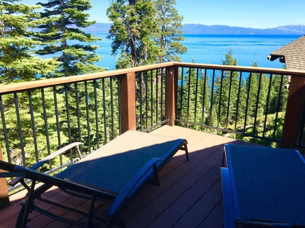 A lakefront cabin in Tahoe with a view, deck looking out with two chairs onto a brilliant turquoise water of the Lake.