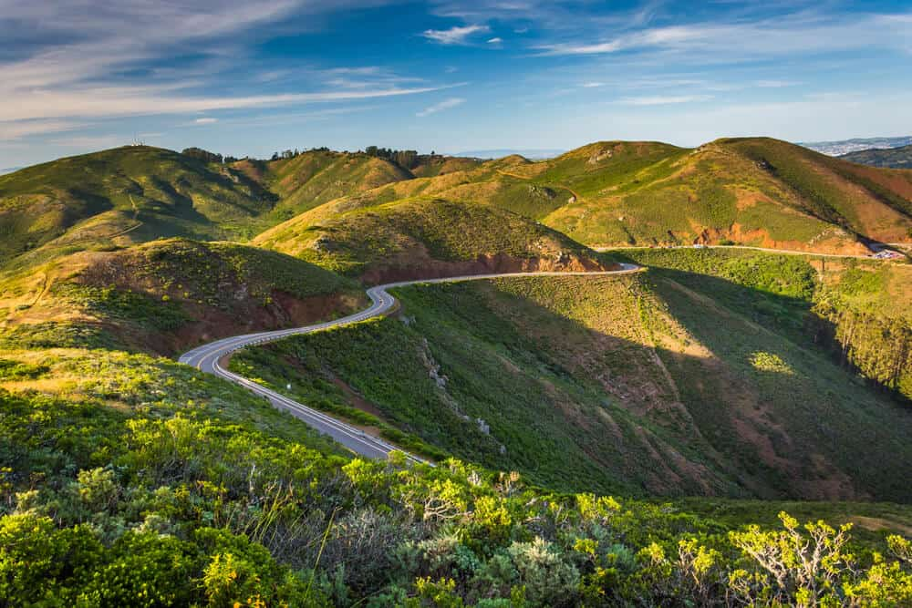 View of Conzelman Road, in Golden Gate National Recreation Area, in San Francisco, California. Green hills with a road snaking through the mountains.
