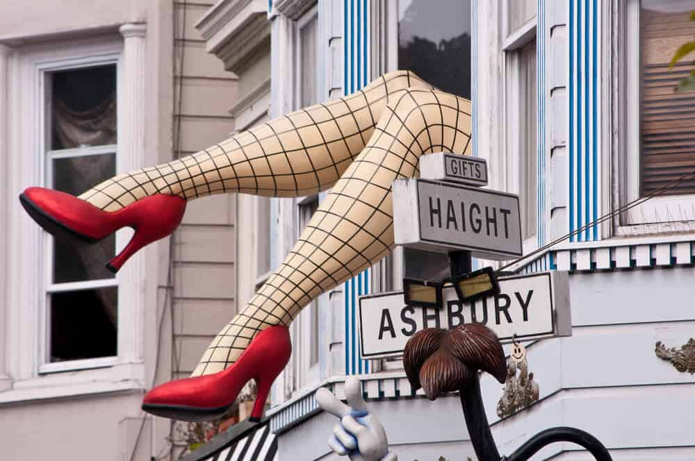 """Street signs which say """"Haight Ashbury"""" with a mannequin of model legs wearing fishnets and red high heels coming out of a window"""