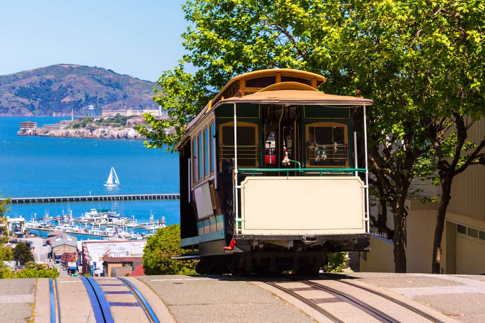 A cable car on Hyde Street going down a steep hill towards the Bay with the island of Alcatraz visible in the distance, as well as a sailboat and a marina.