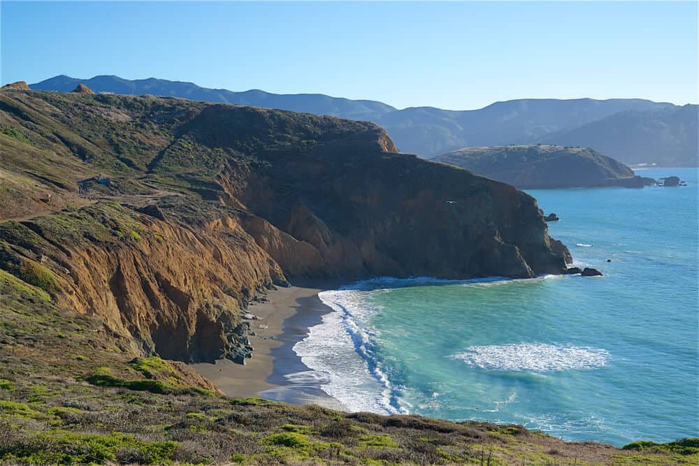 A black sand beach beneath reddish coastal bluffs, with brilliant turquoise water of the Pacific Ocean, on this beloved Bay Area hike to Mori Point.