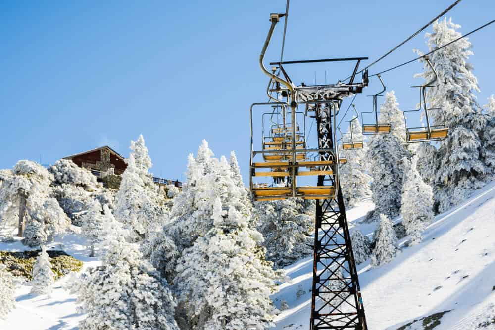 Chair lifts going up on a cable to the top of the Mount Baldy ski resort area, with snow-covered trees on a blue sky day in winter.