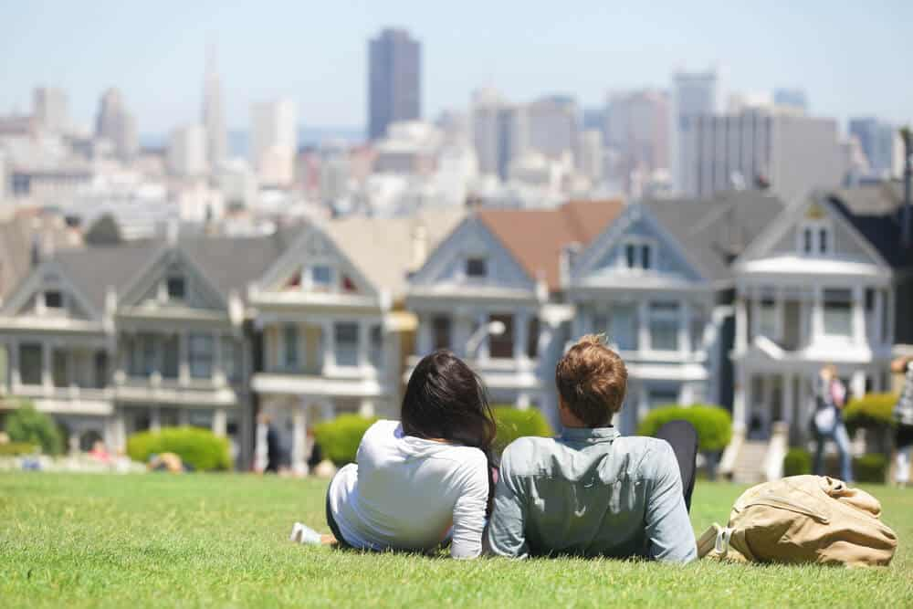 A woman and a man wearing long sleeved shirts and jeans sitting in Alamo Square overlooking the famous Painted Ladies houses and San Francisco skyline.