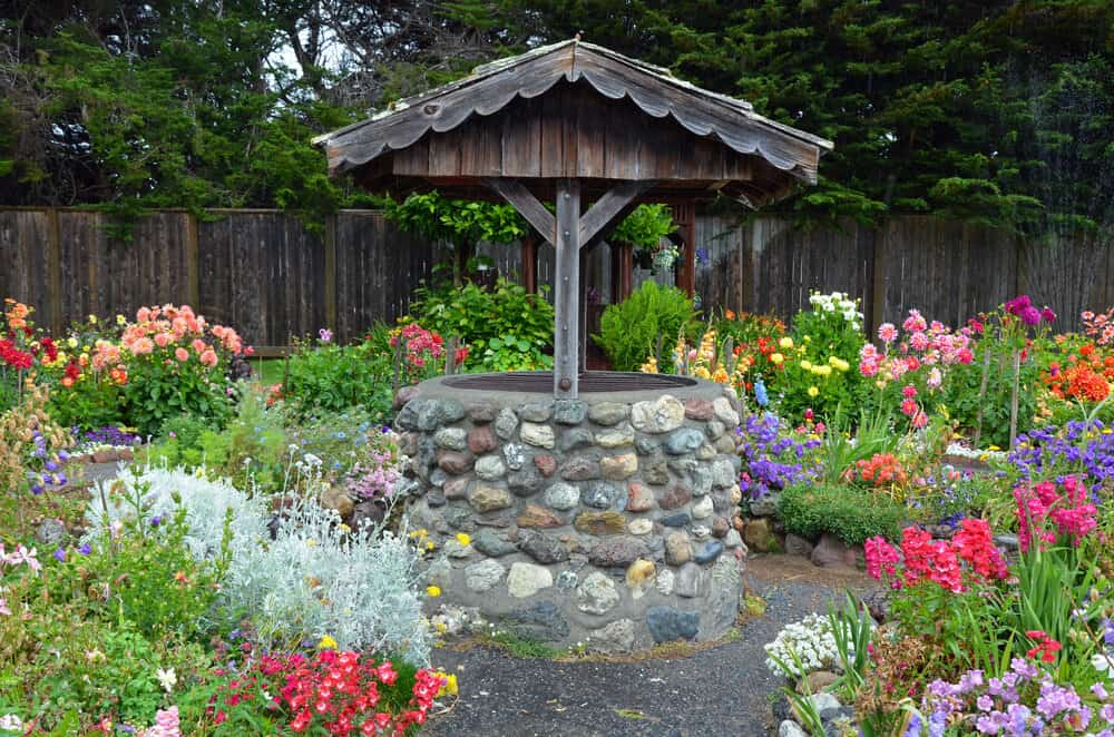 Stone wishing well style well, surrounded by colorful flowers in all shades of the rainbow, in Eureka's Sequoia Park.