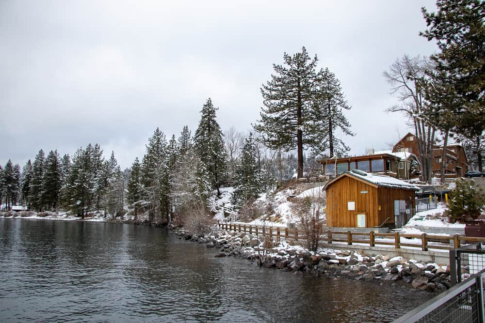 Cabins in Tahoe located on the water in the snow surrounded by water and trees