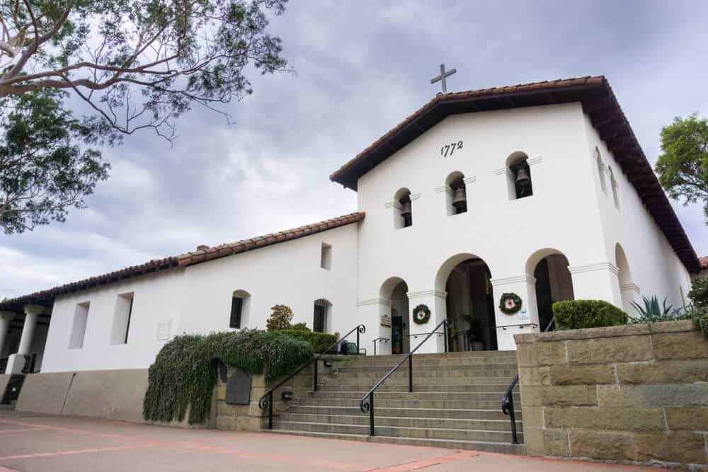 White church building with three bells and a cross in the traditional Spanish architectural style of the 1700s.