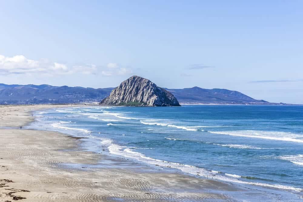 View of Morro Rock from down the. beach, with waves at its base and mountains in the background.