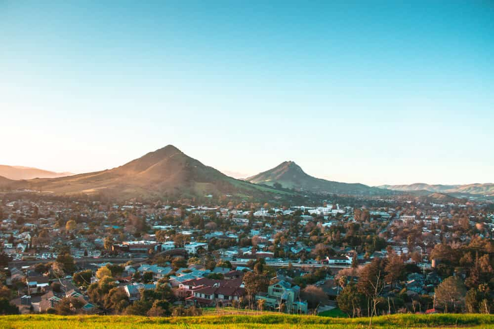 Sunset over the city of San Luis Obispo with two hill peaks in the distance.
