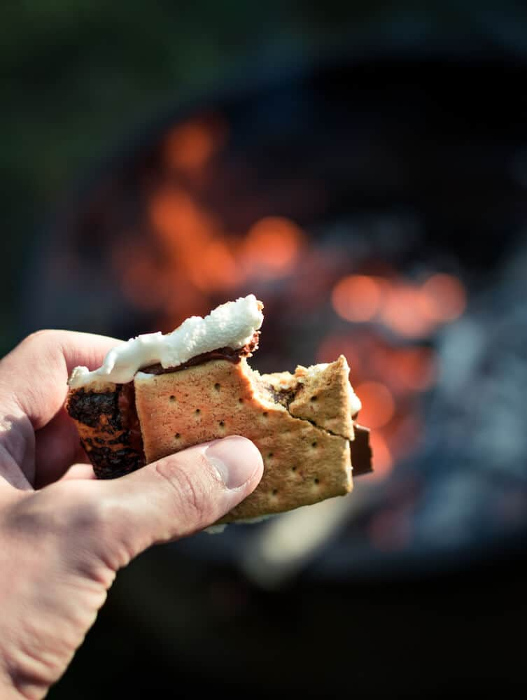 hand holding smores (graham cracker, chocolate and marshmallow) with fire bokeh behind it
