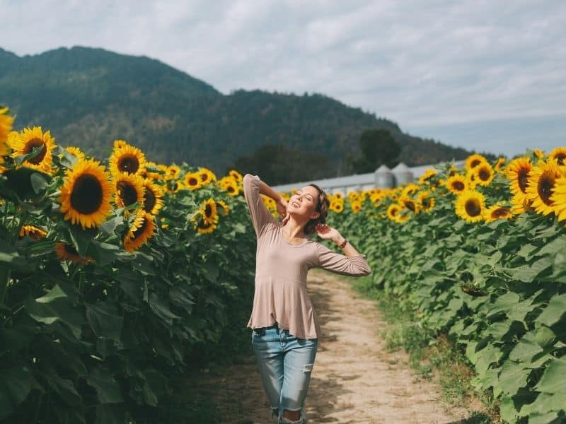 Woman with a beige shirt and jeans smiling in the sun amidst rows of sunflowers in California