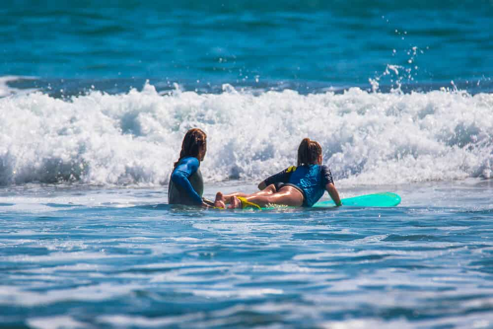 Woman teaching a younger woman how to surf on a turquoise surfboard, both are wearing blue wetsuits.