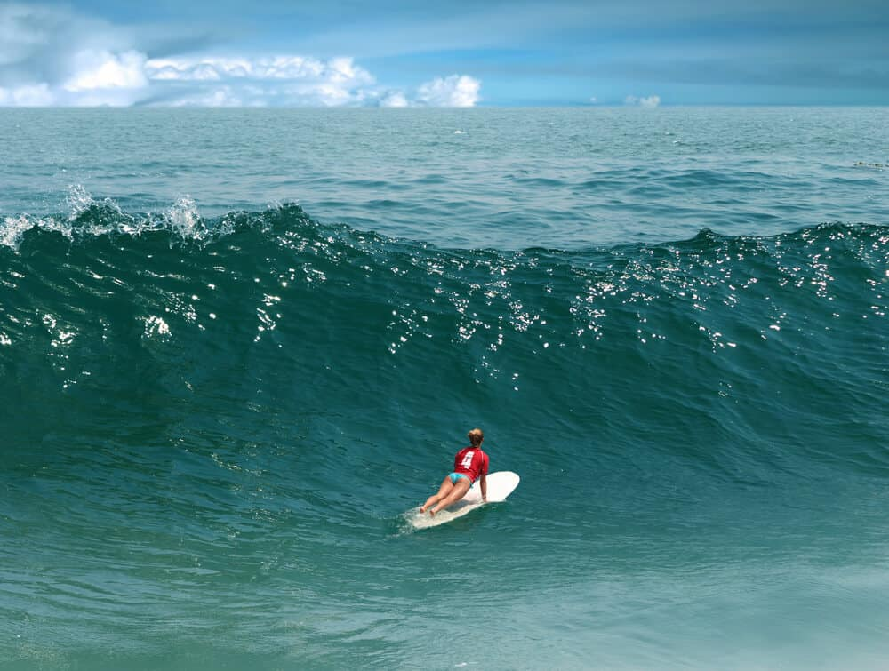 Woman in a red shirt with th number 4 on the back and blue bikini bottoms on a white surfboard, ging over a wave in Malibu
