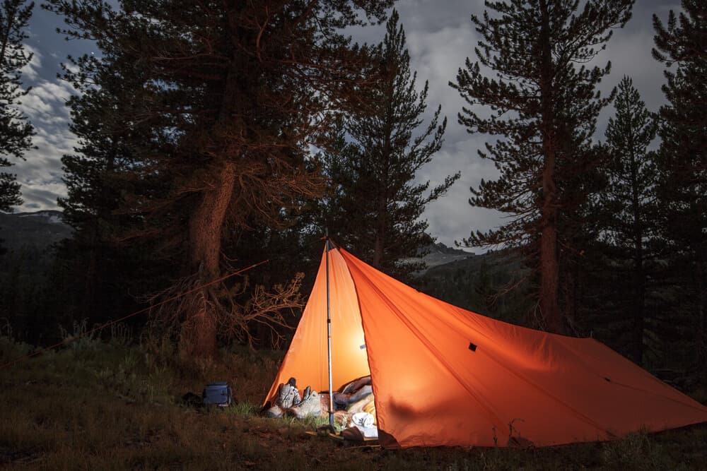 Lit up orange tent in the Yosemite backcountry, with a person inside with a light on. You need a permit for backcountry hiking in Yosemite.