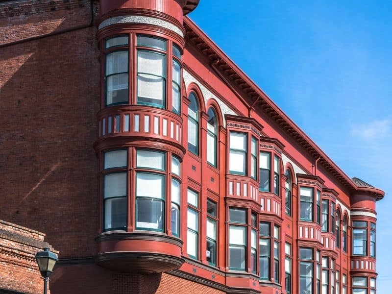 Architectural details of a red building in Eureka's Old Town area, with rounded windows and other Victorian touches