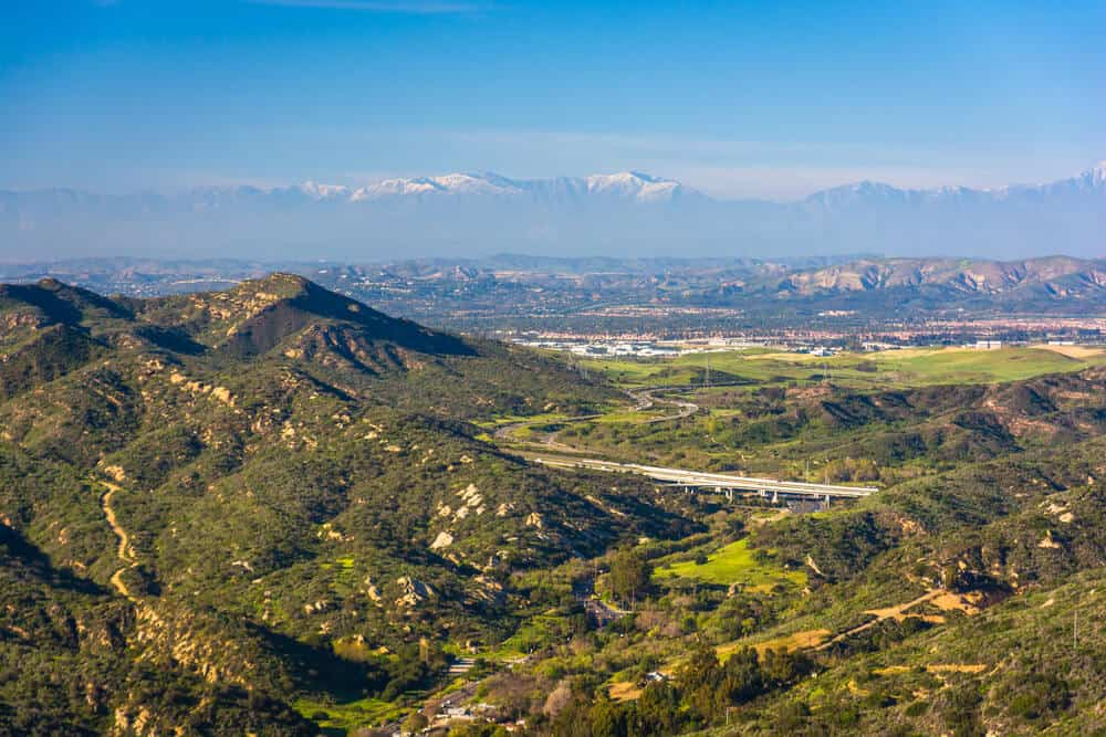 View of mountains, a highway, and hills from the top of the World hike in Orange County's Laguna Beach on a sunny day