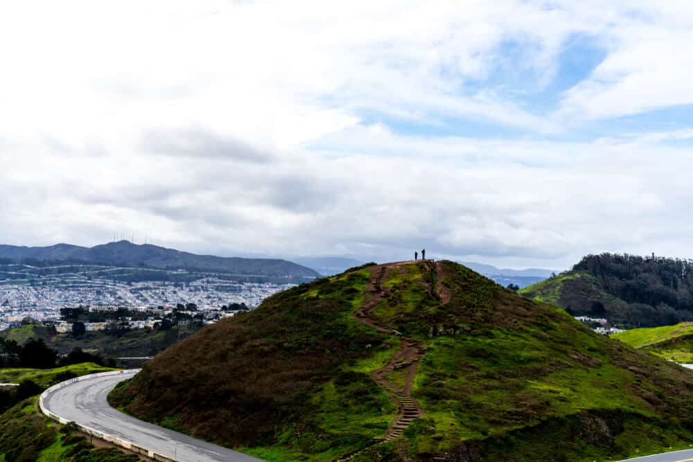 Two small silhouettes at the top of one of the two Twin Peaks, overlooking the city of San Francisco from a popular SF hike