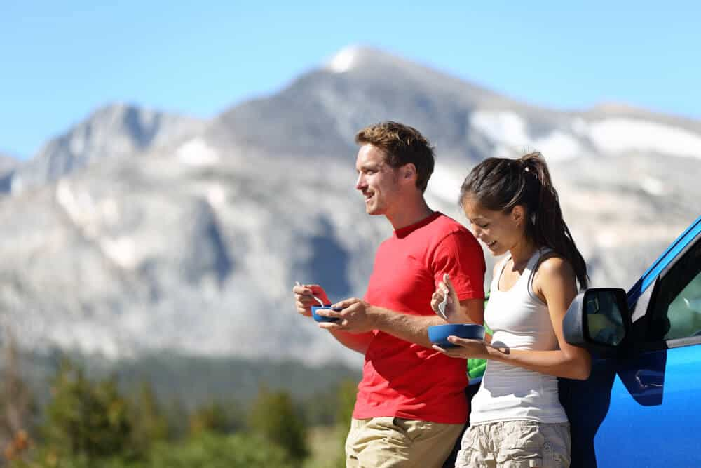 A male and female couple eating out of bowls they have brought from home with a view of Yosemite next to their blue car.
