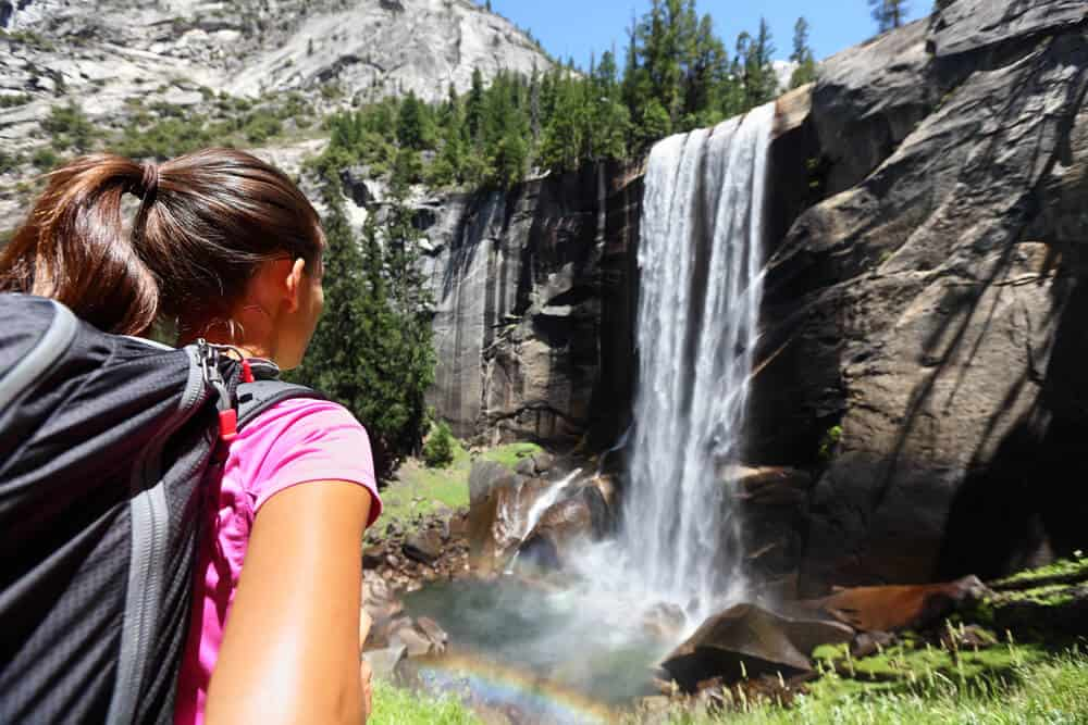Girl with pink shirt and hair in ponytail wearing a day pack, looking at Vernall Falls waterfall making a small rainbow in the mist where the water falls.