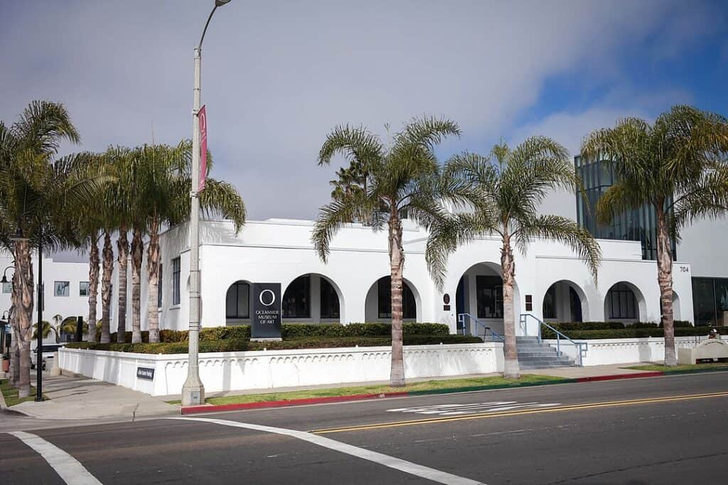White building with archways surrounded by palm trees