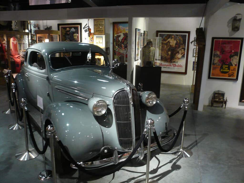 A baby blue vintage car at the Western Museum, surrounded by Western movie posters.