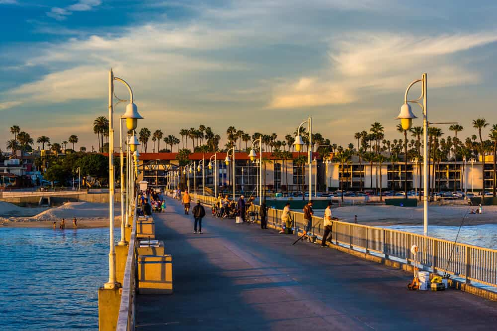 people on belmont pier in long beach at sunset with fishing rods and walking