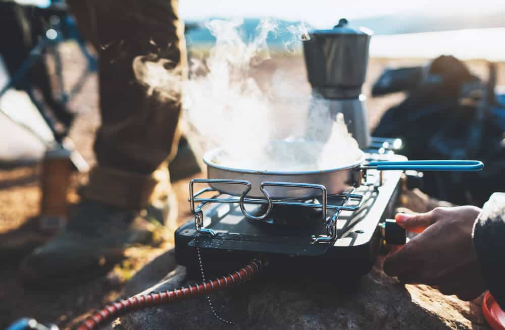Someone using a camping stove with a Mokapot of coffee also being prepared